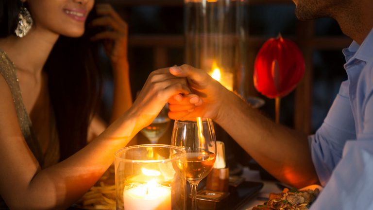(<a href='https://www.bigstockphoto.com/image-113651627/stock-photo-romantic-couple-holding-hands-together-over-candlelight-during-romantic-dinner'>luckybusiness</a>/Big Stock Photo)