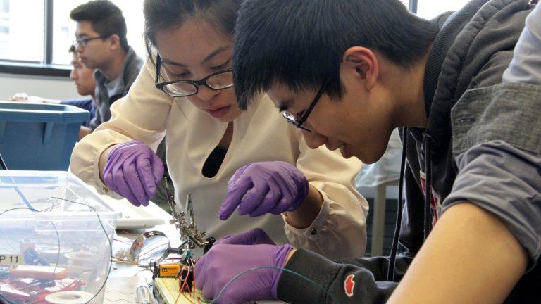 Stephanie Mark and her lab mate maneuvering the severed cockroach leg into position. (Emma Lee/WHYY)