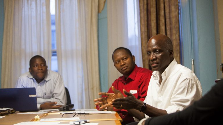 Pastor Moses Dennis (left) chairs a coalition meeting of local West African leaders