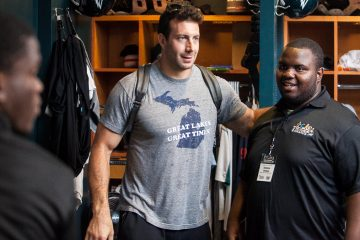 Imhotep Charter's Gordon Thomas meets Eagles linebacker Connor Barwin in the Eagles locker room. (Brad Larrison/for NewsWorks)