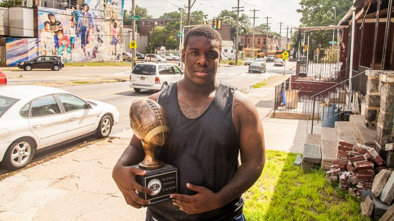 Dawayne Young, who finds himself at the middle of an athletic-eligibility controversy, holds a trophy he received for being the top overall performer at the Next Level Nation Football Camp. (Brad Larrison/for NewsWorks)