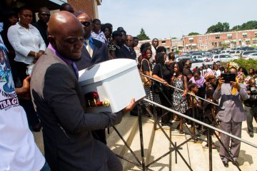 The Gesner Street fire's youngest victim Taj W. Jacque, who was only 49 days old, is carried down the steps of Divine Mercy Parish by a single pallbearer. (Brad Larrison/for NewsWorks)