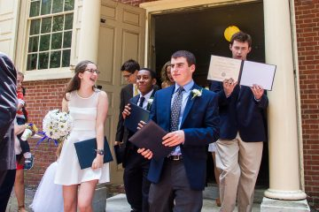 Benjamin Trotto, right, shows off his diploma as he exits the meeting house. (Brad Larrison/for NewsWorks)