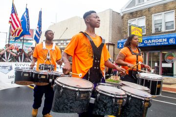 The drumline from Distressed Illusions marches down Rising Sun Avenue (Brad Larrison/for NewsWorks)