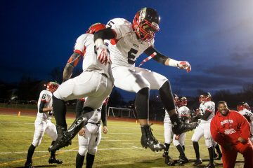 Deandre Scott and Mike Waters get airborne after Imhotep's 20-0 win over Berks Catholic. (Brad Larrison/for NewsWorks)