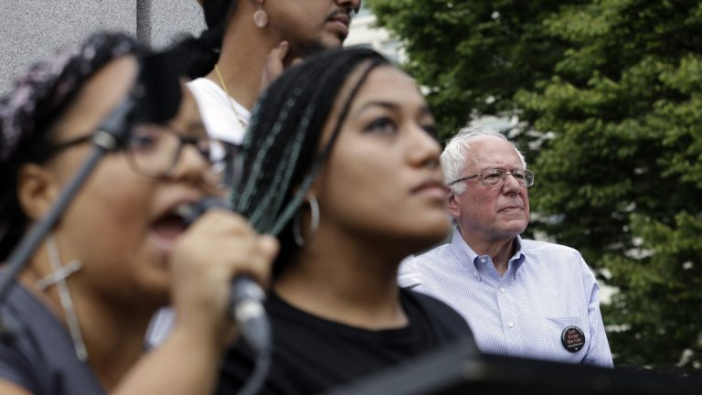 Marissa Johnson, left, speaks as Mara Jacqueline Willaford stands with her. Democratic presidential candidate Sen. Bernie Sanders, I-Vt., stands nearby as the two women take over the microphone at a rally Saturday, Aug. 8, 2015, in downtown Seattle. The women, co-founders of the Seattle chapter of Black Lives Matter, took over the microphone moments after Sanders began speaking. Sanders eventually left the stage without speaking further. (AP Photo/Elaine Thompson)