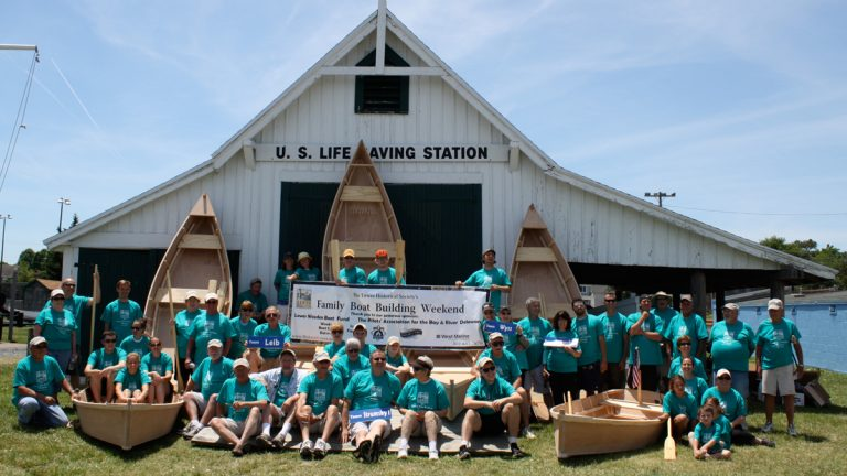 Members of the 2014 boat building groups with their completed vessels.