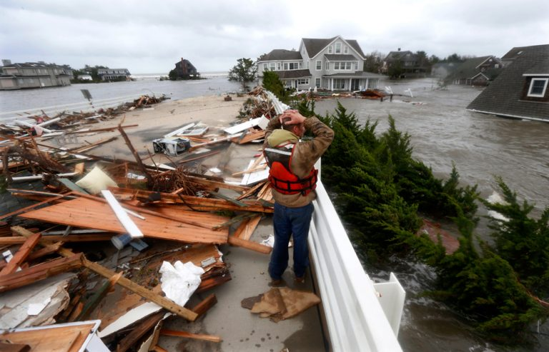Brian Hajeski of Brick, N.J., stares at the stunning devastation, surrounded by the debris of a home that struck the Mantoloking Bridge in Brick during the deadly storm. Photo: Julio Cortez, Associated Press