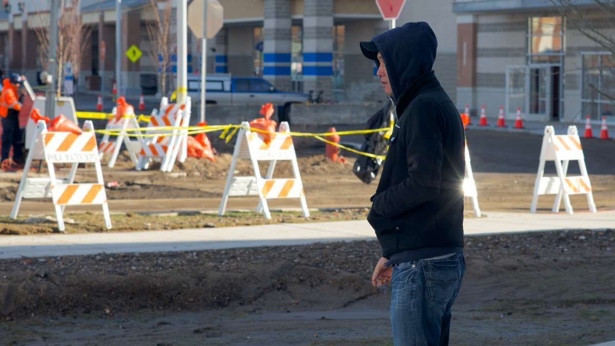 Hair Buzz owner Andy Kim watches PWD work at the site of the water-main break. (Bas Slabbers/for NewsWorks)