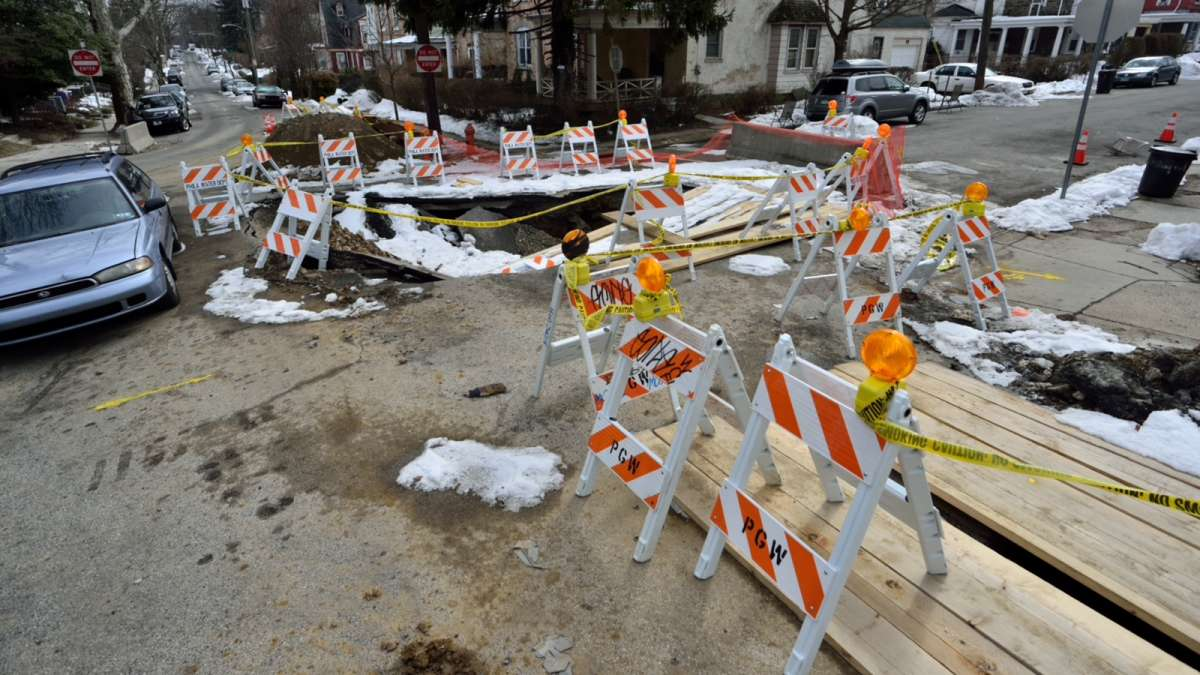 The crater first appeared after an eight-inch water main burst beneath the concrete and damaged a sewer line. (Bas Slabbers/for NewsWorks)