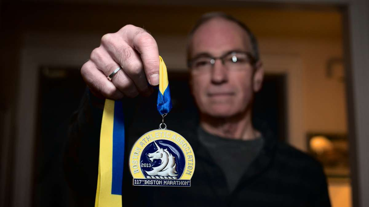 Randy Clever holds his medal from the 2013 Boston Marathon. He will return for the April 21 race. (Bas Slabbers/for NewsWorks)