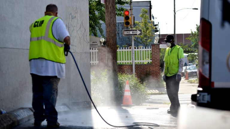City workers Tim Farnon and Jonathan Hurt remove graffiti from a wall on Washington Avenue in Philadelphia. (Bastiaan Slabbers for NewsWorks)