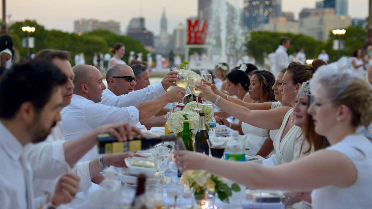 A toast is made as the sun sets over Center City during Philadelphia's fifth Dîner en Blanc.