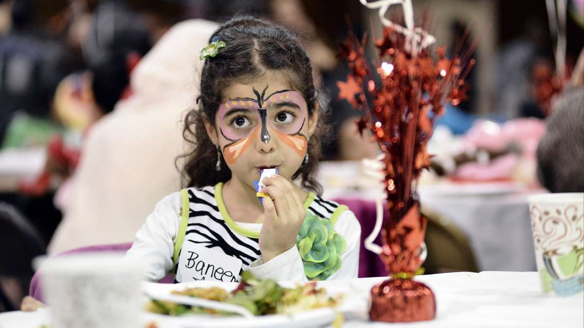 Refugees from all over the world enjoy their first Thanksgiving dinner at the Old Pine Community Center on Sunday. (Bastiaan Slabbers for NewsWorks)