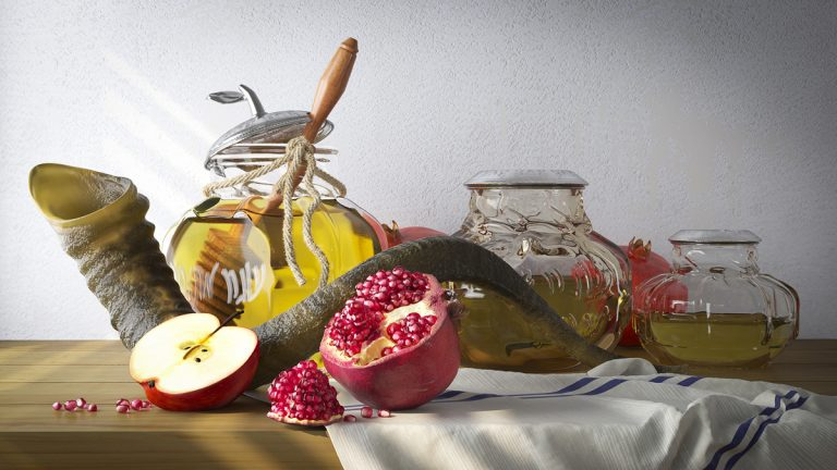 A table is staged for a Rosh Hashana photo including a honey jar with apples