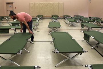 Joel Snyder, housing case manager for the Salvation Army in Norristown, sets up cots for the homeless in the organization's basement gym. (Emma Lee/WHYY)
