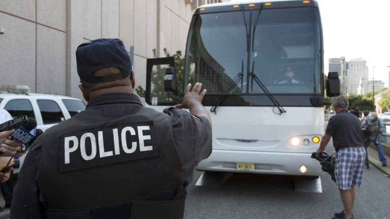 Officer Chester Hampton, inspector for the Philadelphia Police Department truck enforcement division, instructs the bus driver during an inspection. (Charlie Kaier/for NewsWorks)
