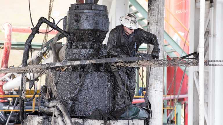 A drill worker covered in Marcellus shale, and drill cuttings seals off a well and cleans the blowout preventer at a Cabot Oil & Gas natural gas drill site in Kingsley, Pa. Washington County has nearly 1,700 Marcellus shale gas wells. (Lindsay Lazarski/WHYY)
