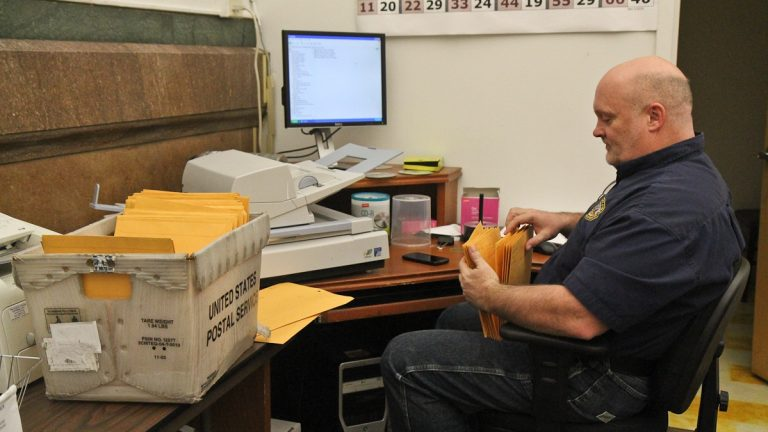 Timothy Dowling, acting supervisor of elections, sorts through candidates' campaign filings Monday. (Kimberly Paynter/WHYY)