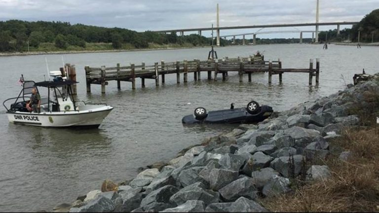 (Overturned vehicle in C & D Canal results in charges of reckless driving and damaging state property against Dover man /DNREC Fish & Wildlife Natural Resources Police Photo)