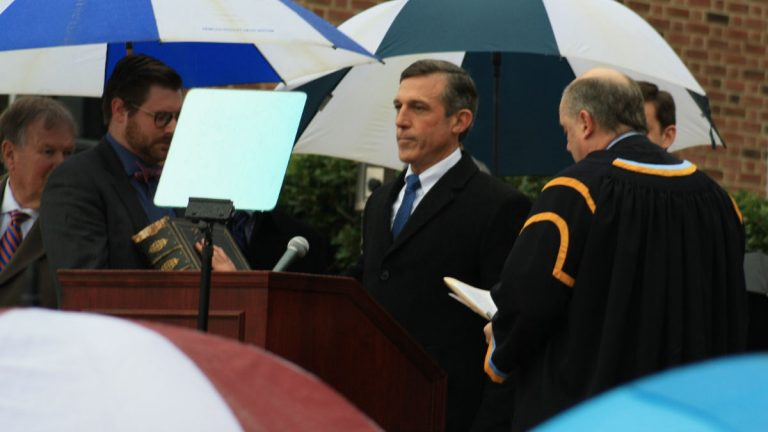 Governor John Carney takes the oath of office from Delaware Chief Justice Leo Strine on a rainy morning outside Legislative Hall in Dover. (Mark Eichmann/WHYY)