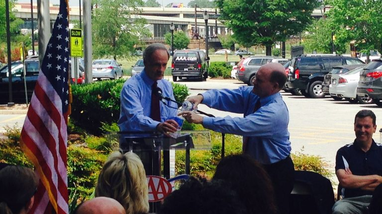Delaware's Senators Carper and Coons use water bottles to demonstrate the challenge facing transportation funding in Congress. (Mark Eichmann/WHYY)