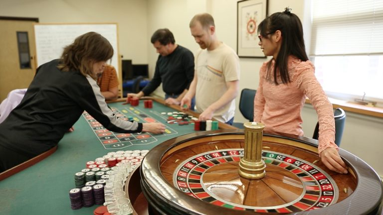 Students gather around the roulette table during the casino training program at Northampton Community College in Bethlehem, Pa. (Lindsay Lazarski/WHYY)