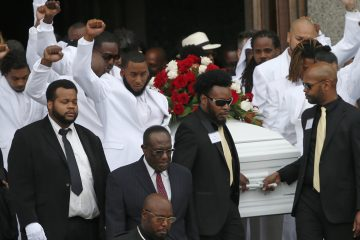 Pall bearers with fists raised carry the casket of  Philando Castile after his funeral service on Thursday