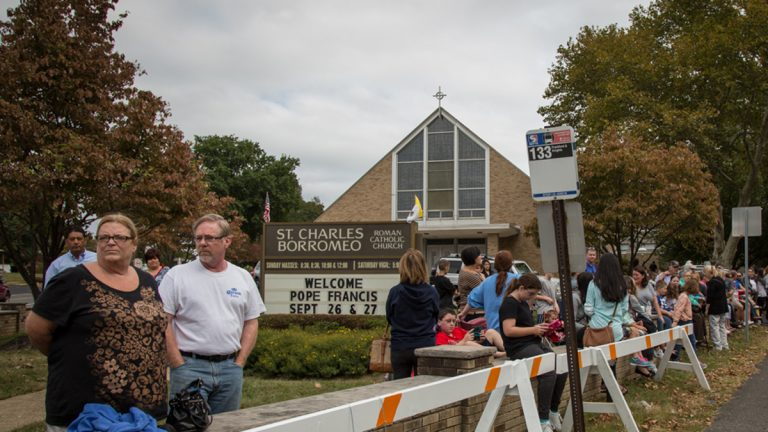 Locals gather across the street from the Shrine of St. Katharine Drexel in hopes that Pope Francis will stop by after praising the saint in his address the day before on the Ben Franklin Parkway. (Emily Cohen/for NewsWorks)