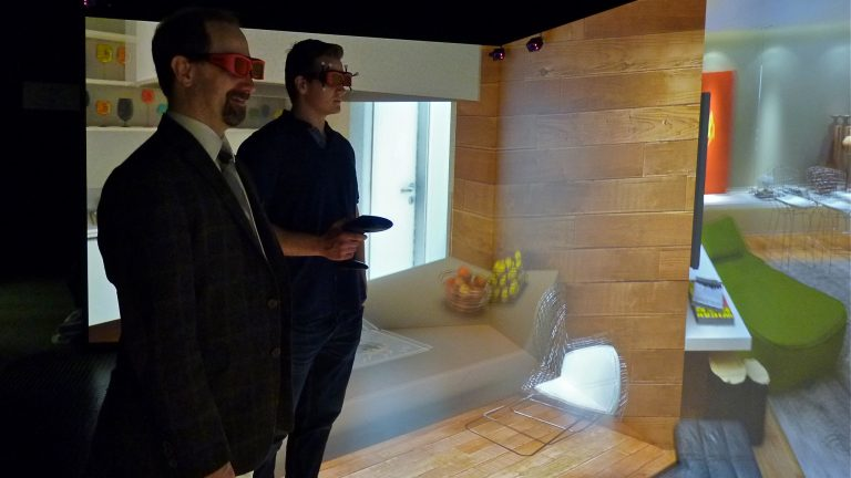 Villanova freshman Charles Walberg (right) explores a virtual room with computer science professor Frank Klassner. They are inside of a 'CAVE immersive learning space
