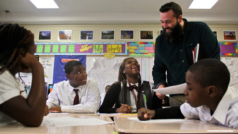 Teacher Andrew Brooking works with students at Blaine Elementary School. (Emma Lee/WHYY)