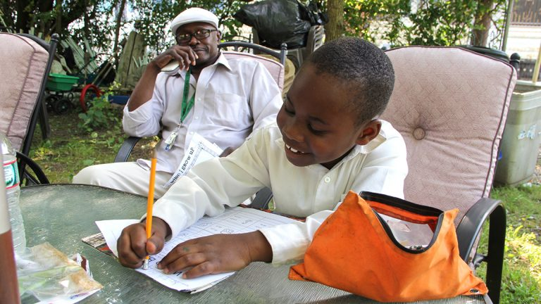 Keith Gray supervises his grandson's homework. Little Keith will be a first grader at Blaine Elementary this fall. (Emma Lee/WHYY)