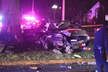 A badly damaged stolen Cadillac rests next to a tree in Newport. The driver was killed crashing the car during a police chase. (John Jankowski/for NewsWorks)