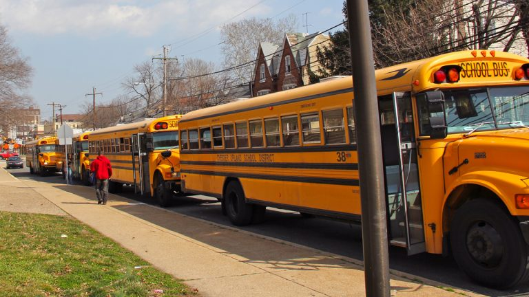 Buses await dismissal on West Ninth Street in front of Chester High School. (Emma Lee/for NewsWorks)