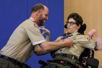 Bob Matcovich pins Christian's new honors onto his son's uniform. (Kimberly Paynter/WHYY)