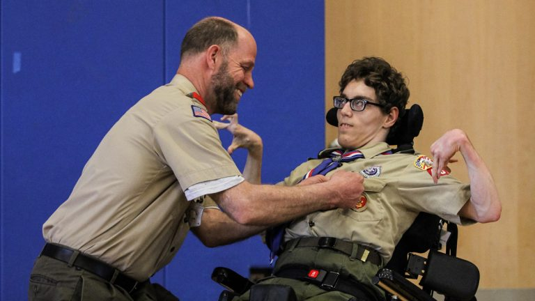 Bob Matcovich pins Christian's new honors onto his son's uniform. (Kimberly Paynter/WHYY)