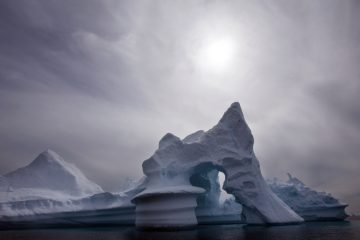 In this 2007 photo, an iceberg is seen off Ammassalik Island in Eastern Greenland. A new assessment of climate change in the Arctic shows the ice in the region is melting faster than previously thought and sharply raises projections of global sea level rise this century. (John McConnico/AP Photo, File)