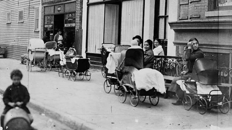 Women and men sitting with baby carriages in front of the Sanger Clinic. (<a href=