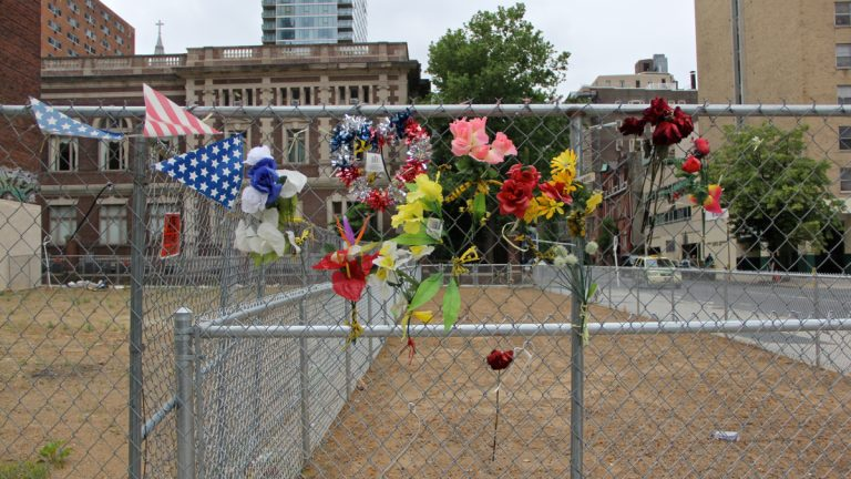 Chain link surrounds the site at 22nd and Market streets where the  Salvation Army Thrift Store collapsed a year ago, killing six. (Emma Lee/WHYY)