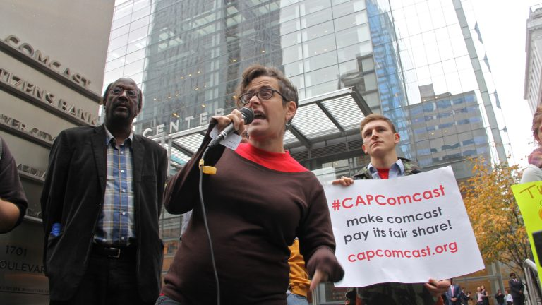 Hannah Sassaman of CAP Comcast leads a rally outside Comcast's Center City headquarters. (Emma Lee/WHYY)