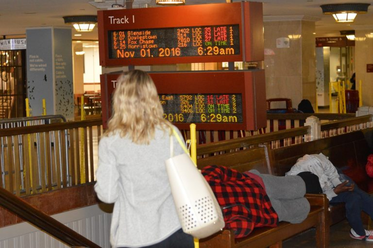 A commuter looks at notices of delays on screen at Suburban Station. (Tom MacDonald/WHYY)