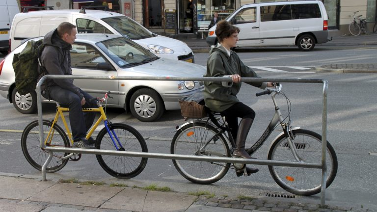 Two cyclists use a foot rest with handles at a major intersection on a downtown Copenhagen street with bicycle-friendly features. (AP Photo/Jan M. Olsen)