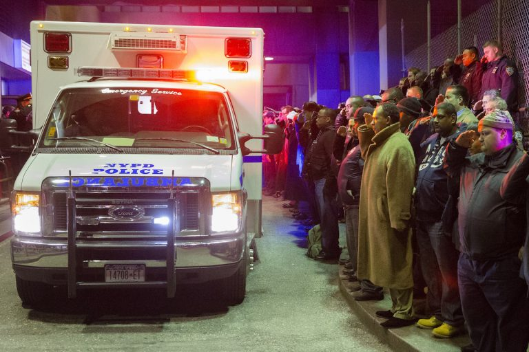Mourners stand at attention as the bodies of two fallen NYPD police officers are transported from Woodhull Medical Center in New York. / AP Photo