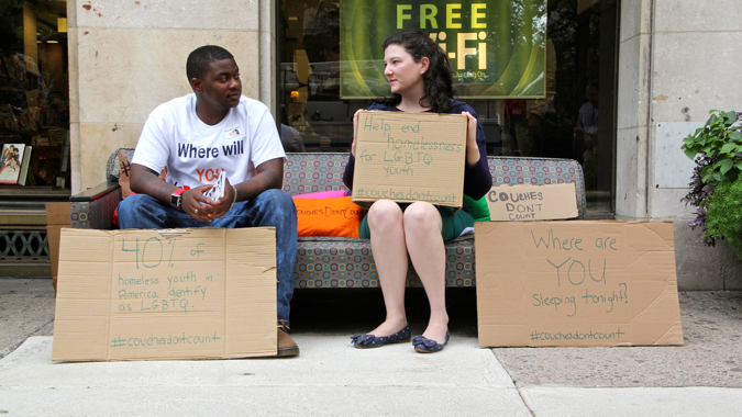 Shiykier Davis, who was homeless at 16 because of his sexual preference, shares a couch with Caitlin Pratt of Valley Youth House. The homeless support organization placed a couch in front of the Barnes & Noble at Rittenhouse Square to draw attention to the plight of LGBT youths who often find themselves 'couch surfing.' (Emma Lee/WHYY)