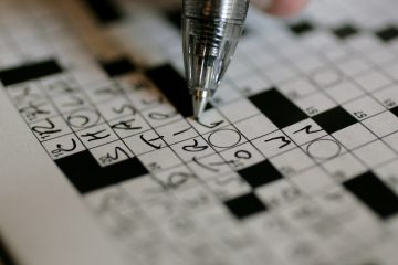 A puzzle fan is shown working on the New York Times crossword puzzle. (AP Photo/Carolyn Kaster
