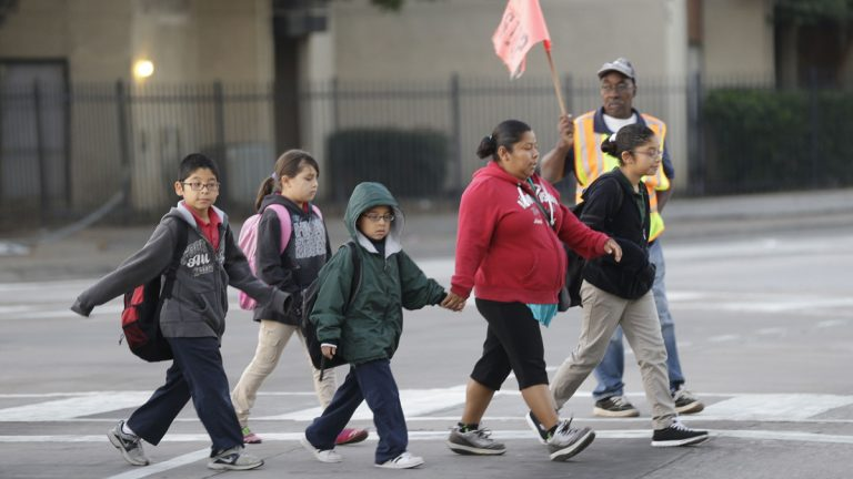 School children use a cross walk while heading to Sam Tasby Middle School in the Vickery Meadow section of Dallas, Tuesday, Oct. 21, 2014. Dallas school officials say four of the five students in their district who were being monitored for Ebola have returned to school after being cleared by health authorities. (AP Photo/LM Otero)