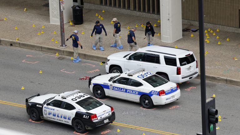 An FBI evidence response team is shown on Saturday investigating the scene of a sniper attack on Dallas police officers. (AP Photo/Gerald Herbert)