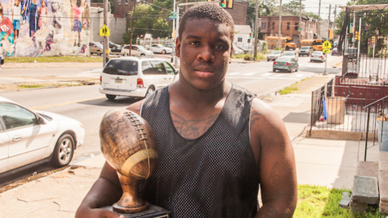 Dawayne Young holds a trophy he received for being the top overall performer at the Next Level Nation Football Camp. (Brad Larrison/for NewsWorks)