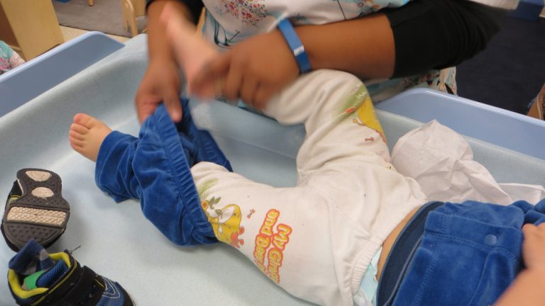 Teachers at the Maternity Care Coalition's Early Head Start prorgram follow a long list of procedures to prevent germ spread at the day care  -- sanitizing diaper-changing tables and wearing gloves to wipe a toddler's nose. (Taunya English/WHYY)