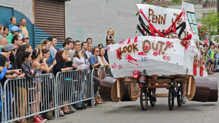 First time Kensington Kinetic Sculpture Derby participants from the Penn Jersey Roller Derby League barrel towards a mud in their zombie skate creation. (Kimberly Paynter/WHYY)